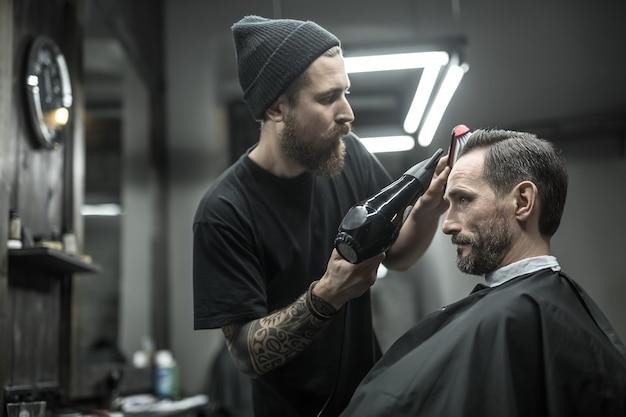 あごひげとタトゥーのある比類のない理髪店が、理髪店の黒いカッティングヘアケープでクライアントの髪を乾かしています
