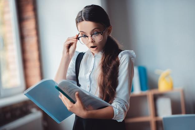 予期しない結果。レポートを押しながらショックを探している眼鏡のブルネットの少女