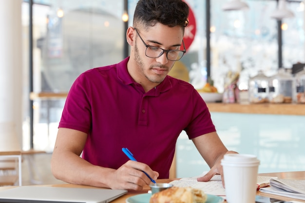 Unexperienced young male worker does remote job, holds blue pen, writes records or remined note in notepad, makes plannings on next week. student prepares for college exam, sits in restaurant