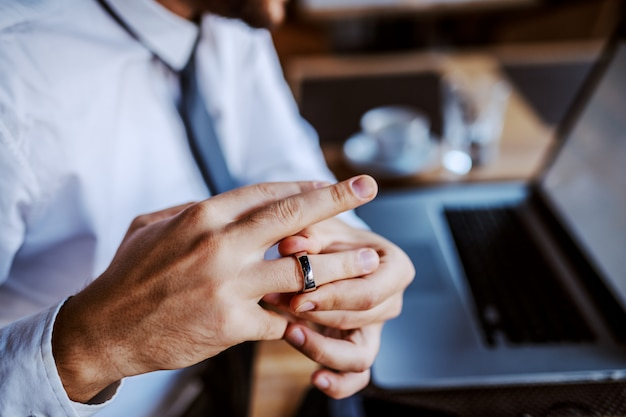 Unfaithful caucasian man in shirt and tie taking off his wedding ring. selective focus on hand.