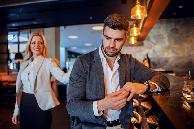 Unfaithful middle-aged man sitting in the bar of a fancy hotel and taking off his wedding ring. woman who is seducing him.