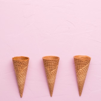 Unfilled waffle ice cream cones on pink surface