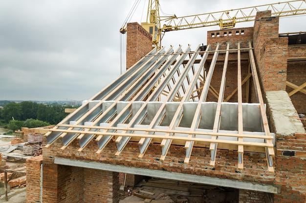 建設中の木造屋根構造の未完成のレンガ造りのアパートの建物。