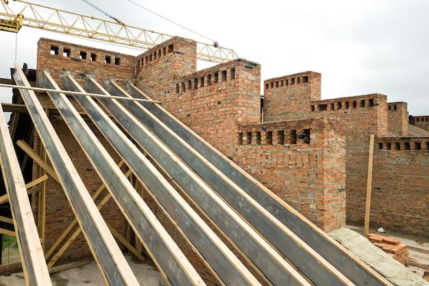 건설 중인 목조 지붕 구조가 있는 미완성 벽돌 아파트 건물입니다.