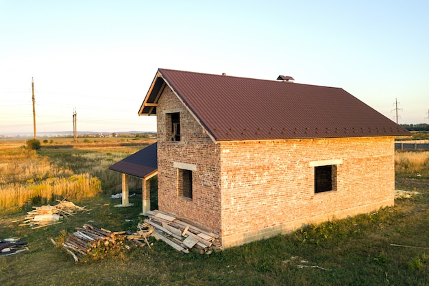Unfinished brick house with roof covered with metal tile sheets under construction.