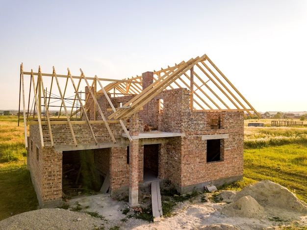 Unfinished brick house with wooden roof structure under construction