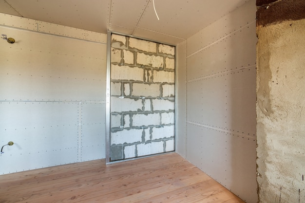 Unfinished brick wall in a room under construction prepared for drywall plates frame installation.