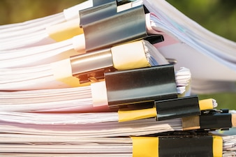 Unfinished documents stacks of paper files on office desk for report papers