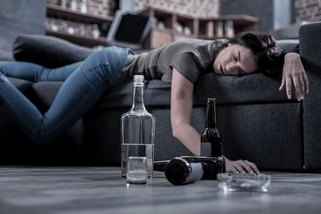 미완성 음료. 백그라운드에서 자고 술 취한 젊은 여자와 함께 바닥에 서있는 보드카의 절반 빈 병의 선택적 초점