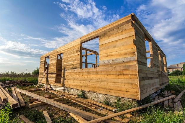 푸른 하늘에 그린 필드에서 건설중인 미완성 된 생태 집. 조용한 지역의 미래 편안한 코티지의 창 개구부로 시멘트와 나무 벽으로 채워진 트렌치.