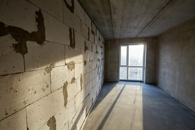 건설중인 건물의 바닥에 폭기 콘크리트 블록과 시멘트 스크 리드로 만든 플라스틱 창 벽이있는 미완성 빈 방