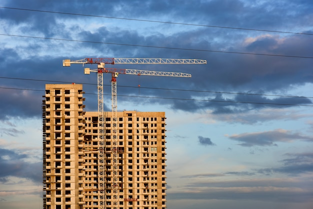 Unfinished high-rise new building and construction cranes, illuminated by the setting sun.