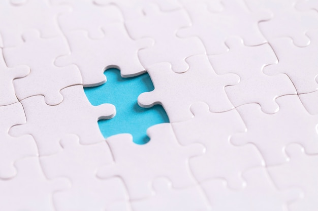Unfinished jigsaw puzzle on blue with copy space
