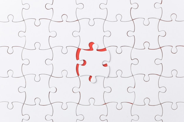 Unfinished jigsaw puzzle texture on red background.