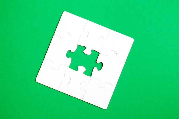 Unfinished puzzle made of white cardboard on a green background and one unsuitable part from another puzzle, one piece is missing, copy space