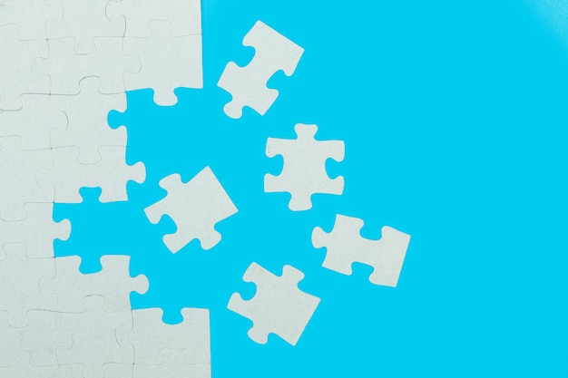 A unfinished puzzle with pieces on a light blue background