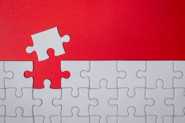 완료 목표에 대 한 빨간색 배경에 미완성 된 흰색 직소 퍼즐 조각