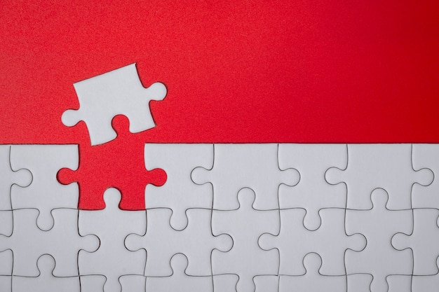 Unfinished white jigsaw puzzle pieces on red background for finish goal
