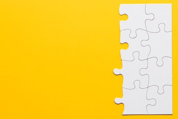 Unfinished white jigsaw puzzle pieces on yellow background