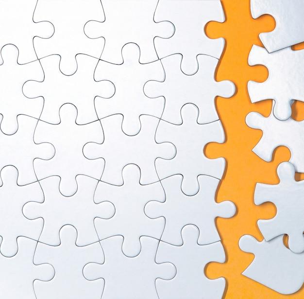 Unfinished white puzzle pieces on orange background