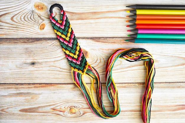 鉛筆の色の選択されたパレットを備えた未完成の織りの友情のブレスレット