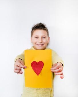 Несосредоточенный мальчик в желтой футболке улыбается и показывает желтую карточку с красным сердцем у белой стены, copyspace