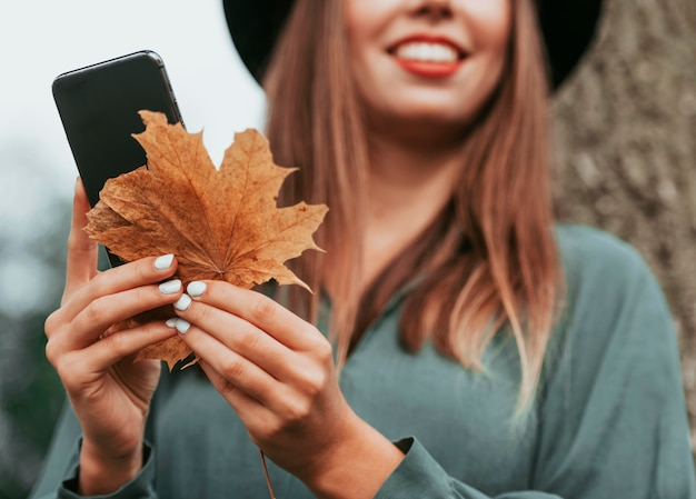 Unfocused smiley woman holding a leaf