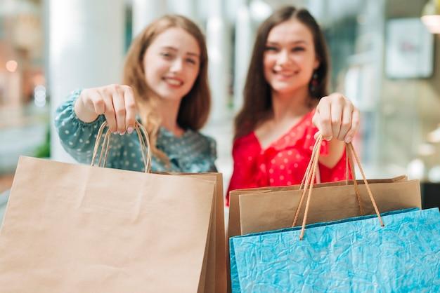 Unfocused women showing bags