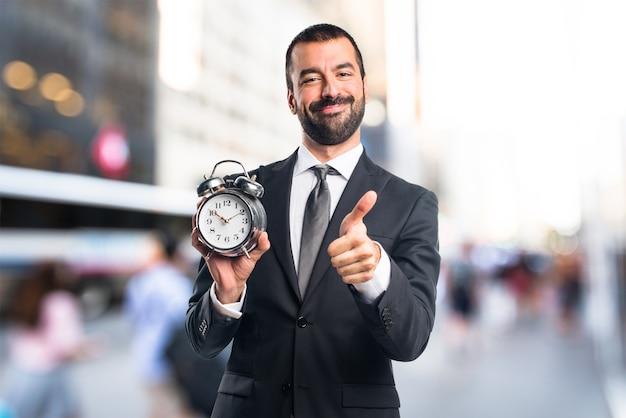 Unfocused背景にヴィンテージ時計を保持するビジネスマン
