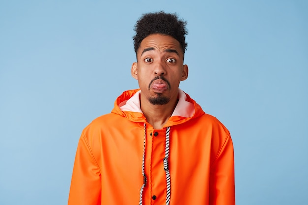 Unhappy african american dark skinned boy wears in orange rain coat,outraged, make grimace, shows tongue stands