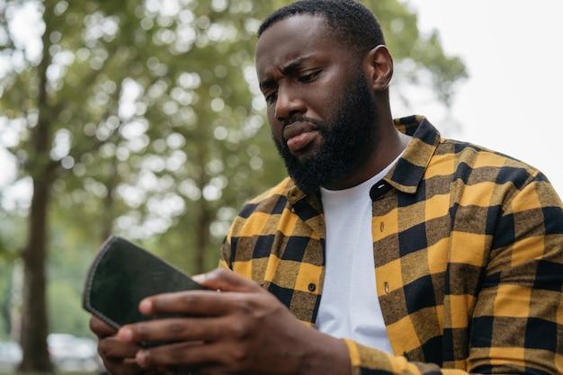 空の財布を持っている不幸なアフリカ系アメリカ人の男。お金の概念はありません