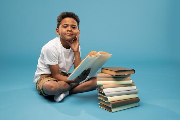 Несчастный африканский мальчик младшего возраста сидит на полу с высокой стопкой книг впереди и держится за нее подбородком