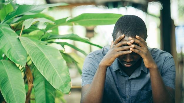 彼の頭に手を握って、困惑した表情を持っている不幸なアフリカ人。黒人男性のストレスと頭痛