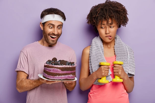 Unhappy afro female temptates her will power, bites lips as looks at tasty baked cake in mans hands, keps to diet, works on loosing weight, stands with dumbbells and towel on neck. sport, nutrition