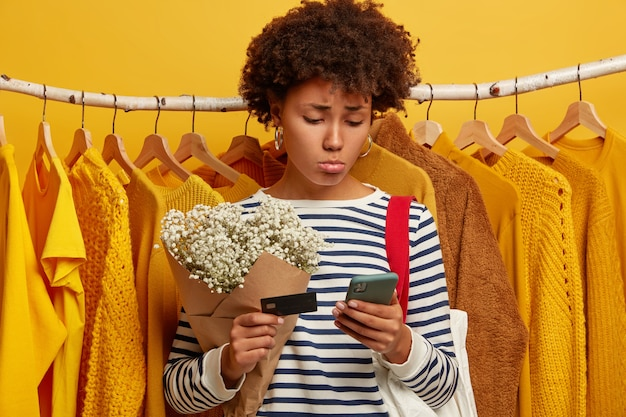 Unhappy afro woman looks sadly at smartphone, holds credit card, cannot make payment online and transfer money, stands near rack with variety of yellow clothes, gets bouquet. sad female buyer