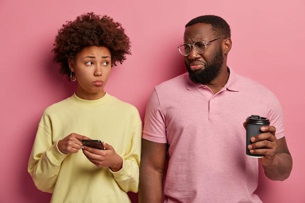 Infelice donna afro mostra qualcosa in smartphone con espressione triste