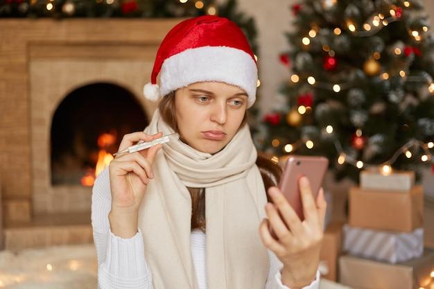 불행하고 건강에 해로운 여자가 손에 장식 된 거실 전화에서 포즈를 취하고, 스마트 폰을 통해 이야기하고, 온도계를 장치 카메라에 표시하고, 크리스마스 휴가 기간 동안 아프다는 것에 실망했습니다.