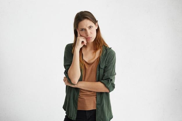 불행하고 화가 난 젊은 여성 직원 또는 고객이 사려 깊은 생각에 잠겨있는 표정을 지으며 좌절감을 느끼고 사원에 손가락을 대고 피곤함을 느낍니다.