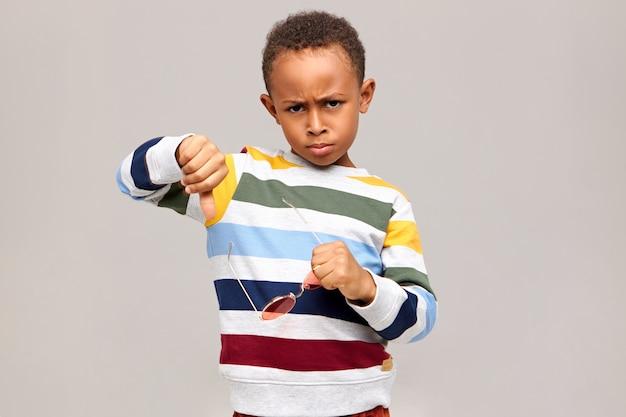 Несчастный сердитый темнокожий мальчик с недовольным взглядом хмурится и делает большой палец вниз жест, выражающий неприязнь и неодобрение, недовольный плохим качеством дешевых сломанных солнцезащитных очков