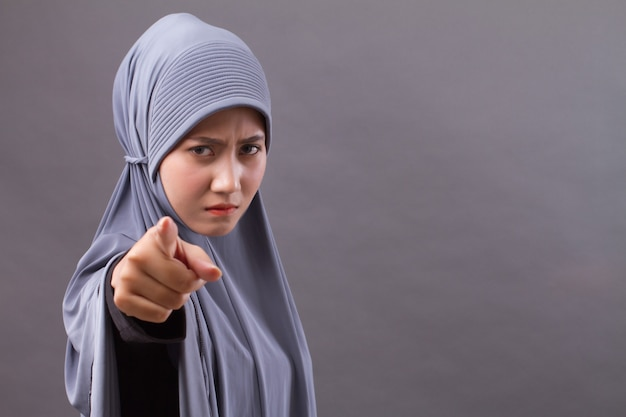Unhappy angry frustrated upset muslim woman pointing at you, with hijab or head scarf