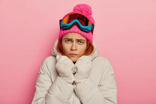 불행한 화난 젊은 여성의 불만, 흰색 따뜻한 코트와 장갑을 착용하고 추위에 떨림