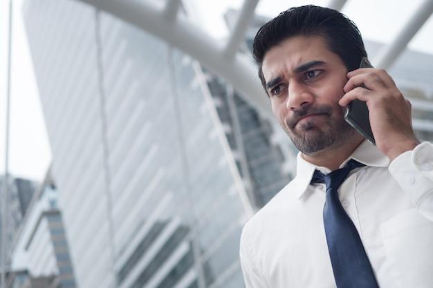 Несчастный азиатский деловой человек говоря умный телефон; портрет несчастного грустного неудачливого серьезного азиатского, индийского бизнесмена, говорящего по смартфону; переговоры, деловая сделка, сделка, коммуникационная концепция