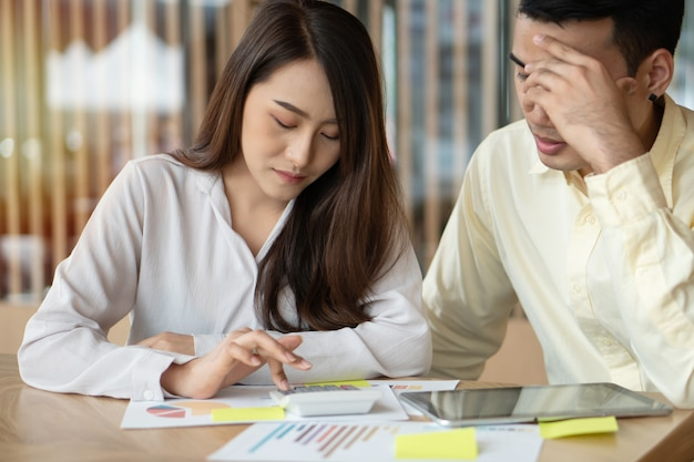 Unhappy asian couples are calculating income and expenses to cut unnecessary expenses.