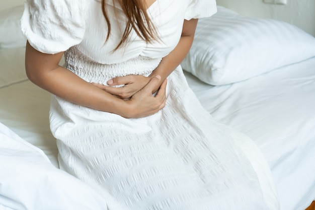 Unhappy asian female sitting on bed and suffering from stomachache. health problem concept