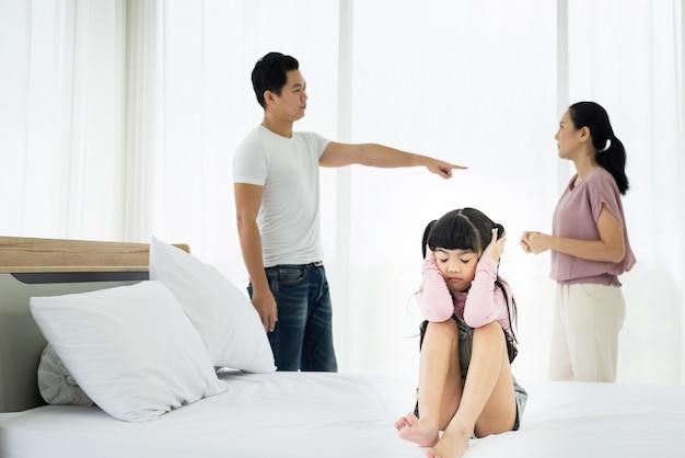 불행한 아시아 여자 아이는 부모가 백그라운드에서 인수를 갖는 그녀의 귀를 커버