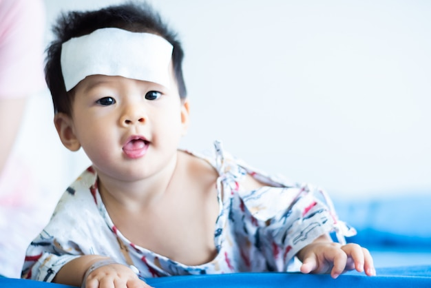 Unhappy asian little baby sick with cool fever jel pad on forehead