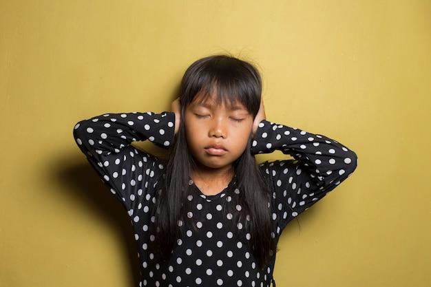 Unhappy  asian little girl close her ears