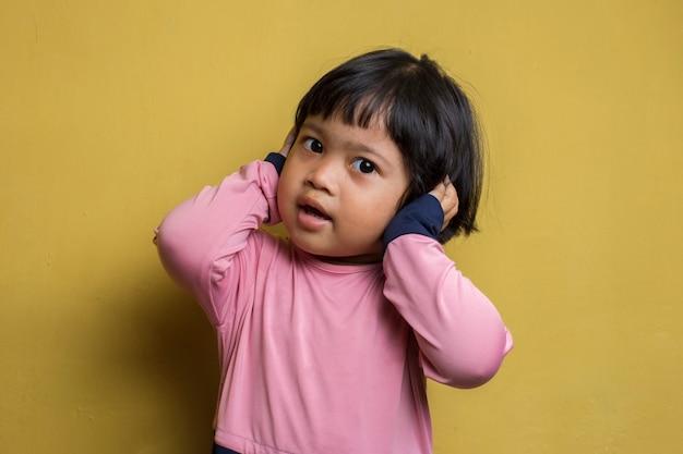 Несчастная азиатская маленькая девочка закрыла уши
