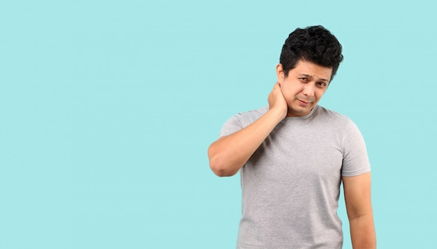 Unhappy asian man suffering from neck pain on light blue background in studio
