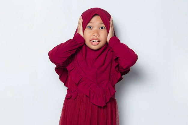 Unhappy asian muslim little girl close her ears isolated on white background